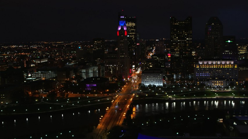 5.7K aerial video of passing by the city skyline, and bridge spanning the river at night, Downtown Columbus, Ohio Aerial Stock Footage | DX0001_002799