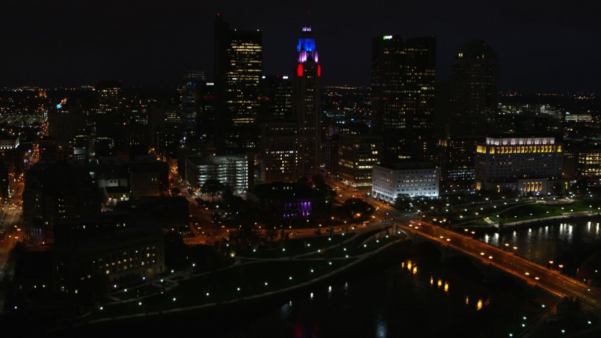 5.7K aerial video of flying by LeVeque Tower and bridge spanning the river at night, Downtown Columbus, Ohio Aerial Stock Footage | DX0001_002801