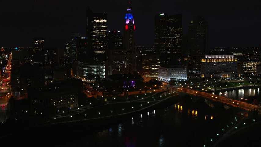 5.7K stock footage aerial video of passing by LeVeque Tower and bridge spanning the river at night, Downtown Columbus, Ohio Aerial Stock Footage | DX0001_002802
