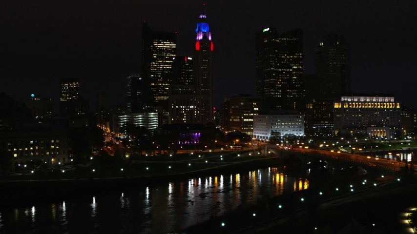 5.7K aerial video of LeVeque Tower and bridge spanning the river at night seen during descent, Downtown Columbus, Ohio Aerial Stock Footage | DX0001_002804