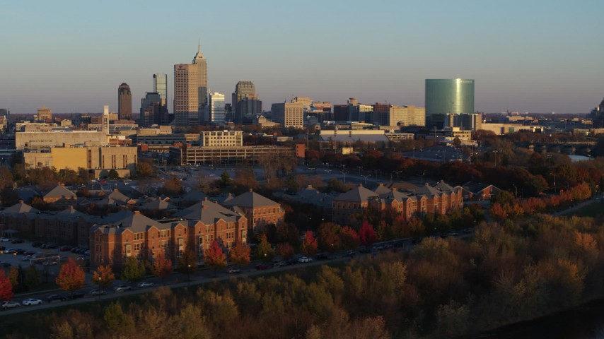5.7K aerial video of a view of the city's skyline at sunset, descend to reveal White River, Downtown Indianapolis, Indiana Aerial Stock Footage | DX0001_002924