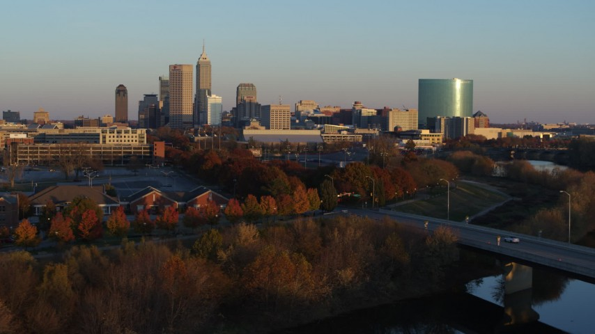 5.7K stock footage aerial video of the city's skyline at sunset seen from White River, ascend over bridge, Downtown Indianapolis, Indiana Aerial Stock Footage | DX0001_002925