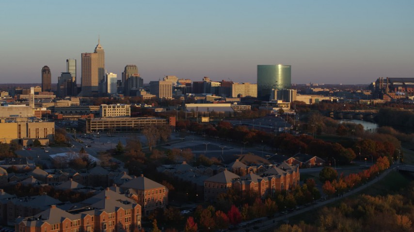 5.7K stock footage aerial video of the city's skyline at sunset seen while ascending from White River, Downtown Indianapolis, Indiana Aerial Stock Footage | DX0001_002927