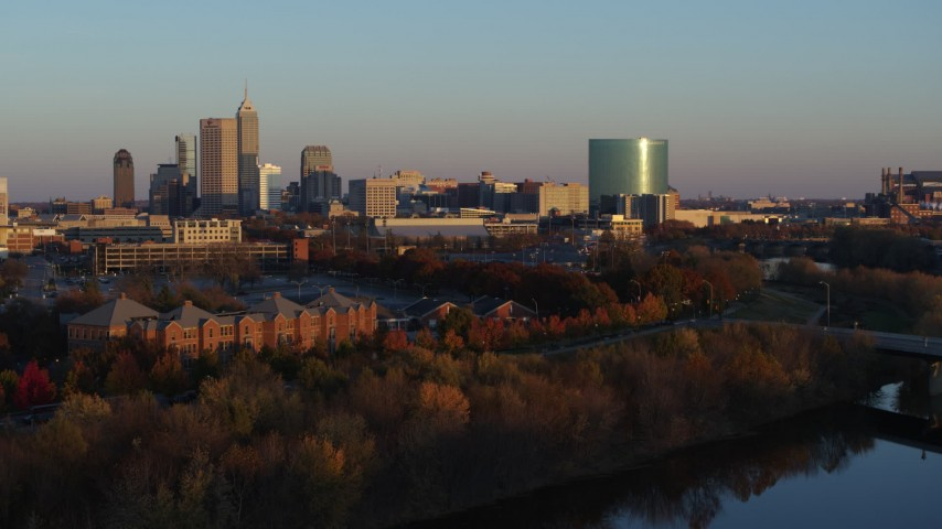 5.7K aerial video of the city's skyline at sunset, seen during descent toward White River, Downtown Indianapolis, Indiana Aerial Stock Footage DX0001_002929