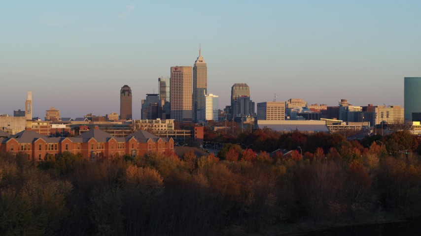 5.7K stock footage aerial video of the city's skyline at sunset, seen from trees, Downtown Indianapolis, Indiana Aerial Stock Footage | DX0001_002930