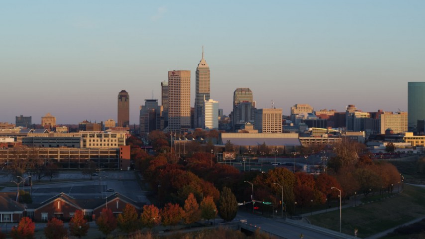 5.7K stock footage aerial video of the city's skyline at sunset, seen during ascent from trees, Downtown Indianapolis, Indiana Aerial Stock Footage | DX0001_002931