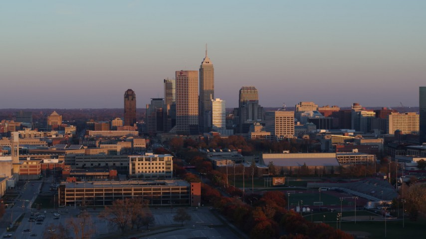 5.7K stock footage aerial video of passing the city's downtown skyline at sunset before ascent, Downtown Indianapolis, Indiana Aerial Stock Footage | DX0001_002934