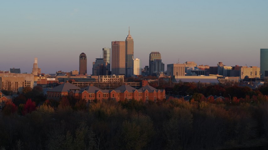 5.7K aerial video descend behind trees with wide view of the city's downtown skyline at sunset, Downtown Indianapolis, Indiana Aerial Stock Footage | DX0001_002936