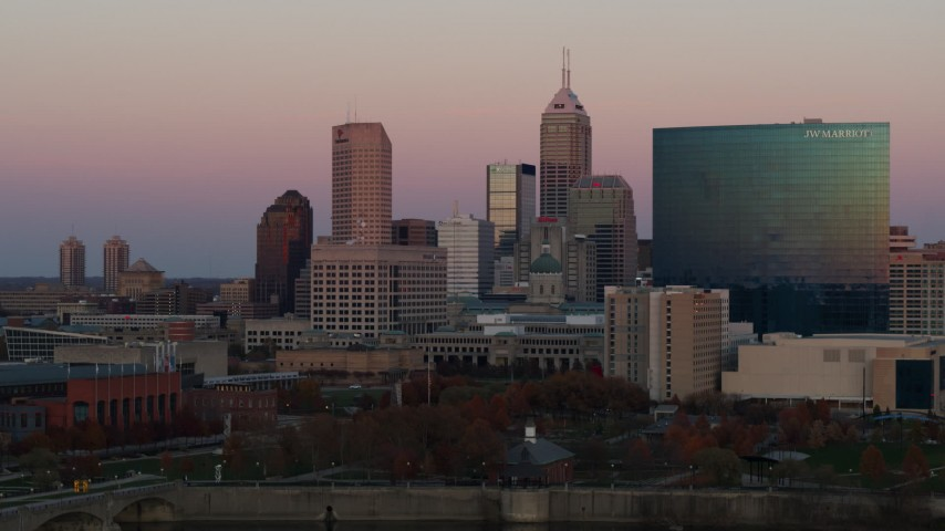5.7K stock footage aerial video pan and ascend by hotel and the city's skyline at sunset, Downtown Indianapolis, Indiana Aerial Stock Footage | DX0001_002938