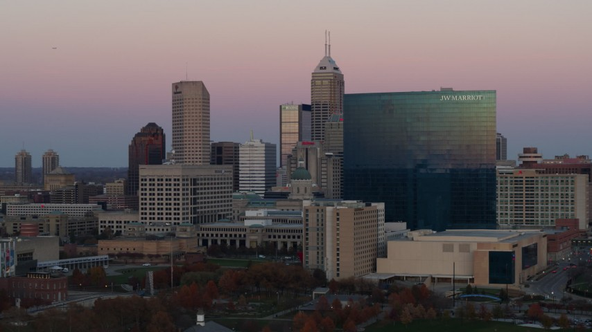 5.7K stock footage aerial video of flying by hotel and the city's skyline at sunset, Downtown Indianapolis, Indiana Aerial Stock Footage | DX0001_002939