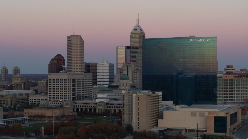 5.7K stock footage aerial video of flying by hotel to reveal the city's skyline at sunset, Downtown Indianapolis, Indiana Aerial Stock Footage | DX0001_002940