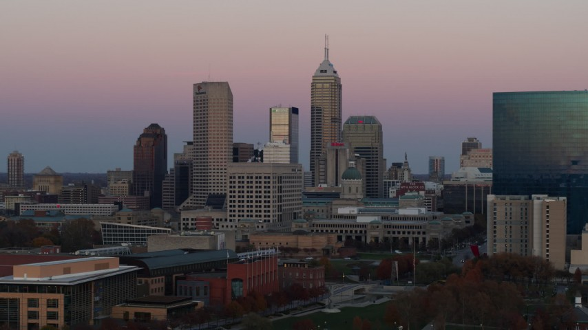 5.7K stock footage aerial video of flying away from and by hotel and city's skyline at sunset, Downtown Indianapolis, Indiana Aerial Stock Footage | DX0001_002941