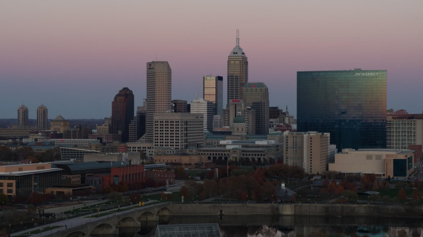 5.7K aerial video of flying away from hotel and city's skyline at sunset, Downtown Indianapolis, Indiana Aerial Stock Footage | DX0001_002942