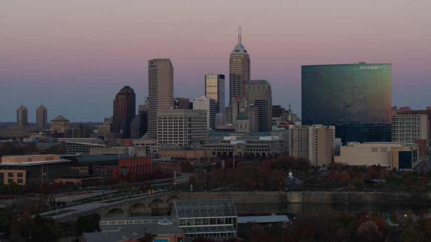 5.7K stock footage aerial video of descending near hotel and city's skyline at sunset, Downtown Indianapolis, Indiana Aerial Stock Footage | DX0001_002943