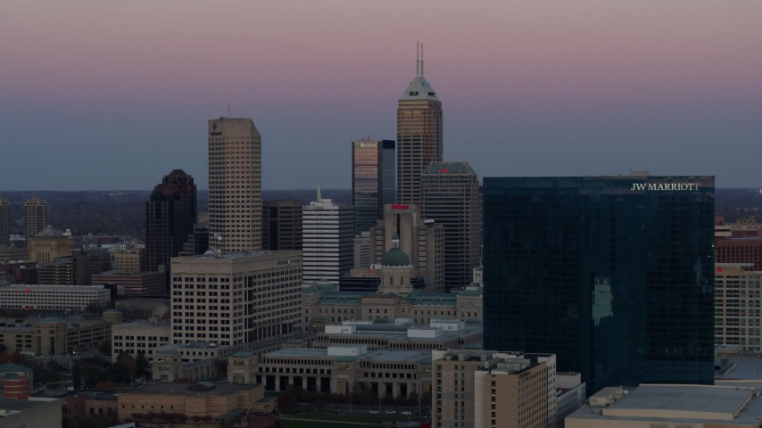 5.7K aerial video of passing by city's skyline and hotel at sunset, Downtown Indianapolis, Indiana Aerial Stock Footage | DX0001_002945