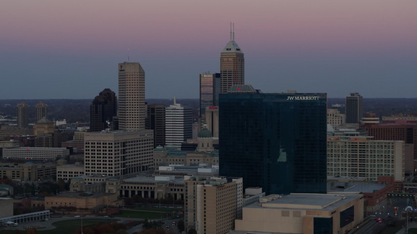 5.7K aerial video of a reverse view of a hotel at sunset, and then flyby skyline in Downtown Indianapolis, Indiana Aerial Stock Footage | DX0001_002946
