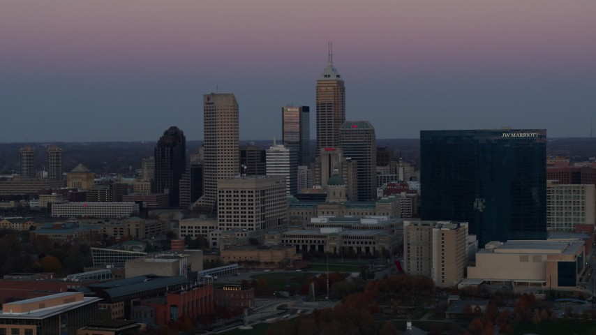 5.7K stock footage aerial video flying by the city's skyline and a hotel at sunset in Downtown Indianapolis, Indiana Aerial Stock Footage | DX0001_002948