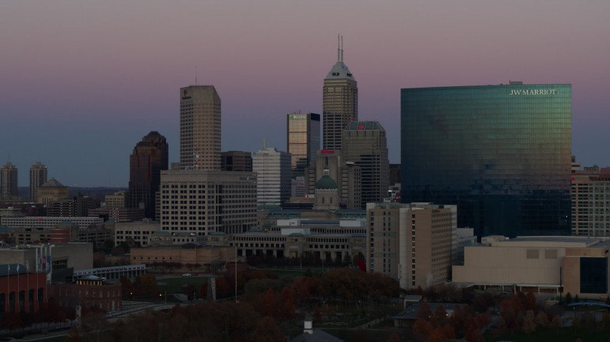 5.7K stock footage aerial video approach the city's skyline and a hotel at sunset in Downtown Indianapolis, Indiana Aerial Stock Footage | DX0001_002949