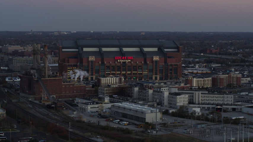 5.7K aerial video slowly flying away from a football stadium at sunset, Downtown Indianapolis, Indiana Aerial Stock Footage | DX0001_002953