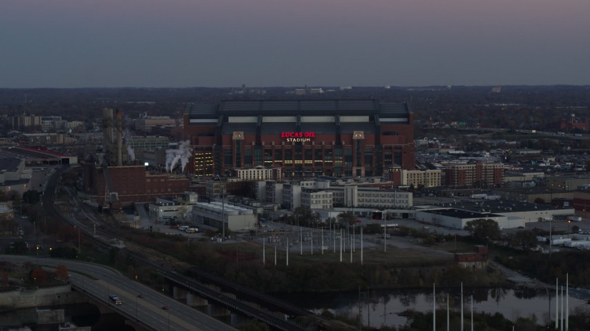 5.7K stock footage aerial video reverse view and flyby of a football stadium at sunset, Downtown Indianapolis, Indiana Aerial Stock Footage | DX0001_002954
