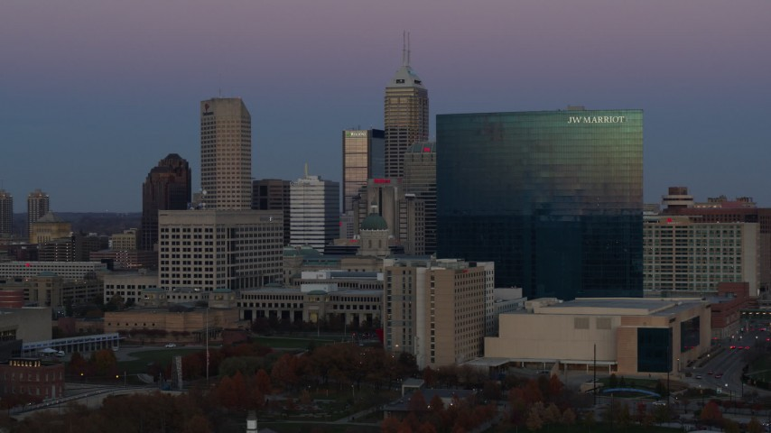 5.7K aerial video slow pass by hotel at twilight, Downtown Indianapolis, Indiana skyline in background Aerial Stock Footage | DX0001_002956
