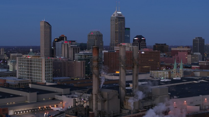 5.7K stock footage aerial video flyby smoke stacks for view of city skyline at twilight in Downtown Indianapolis, Indiana Aerial Stock Footage | DX0001_002960