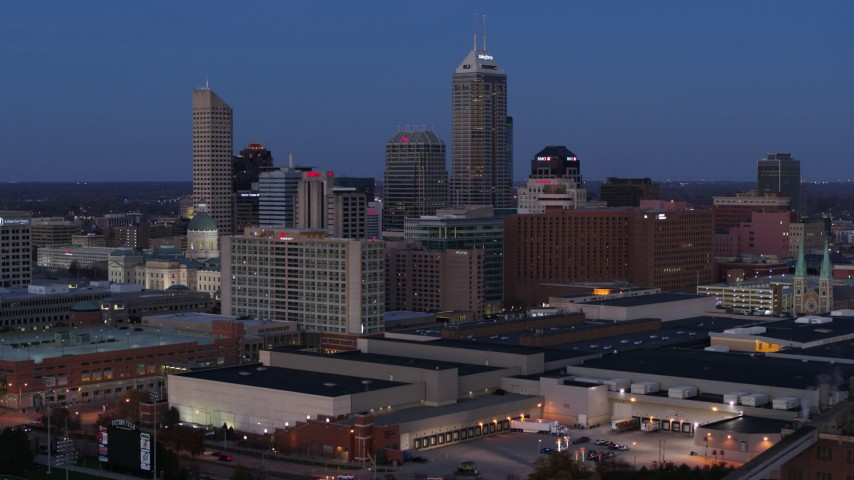5.7K aerial video fly away from and past city skyline at twilight to reveal smoke stacks, Downtown Indianapolis, Indiana Aerial Stock Footage | DX0001_002961