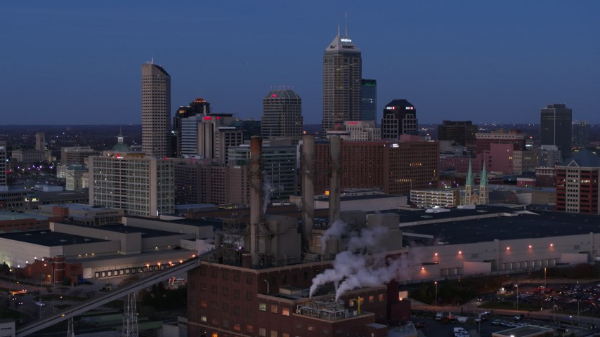 5.7K stock footage aerial video fly past smoke stacks at twilight with skyline in background, Downtown Indianapolis, Indiana Aerial Stock Footage | DX0001_002962