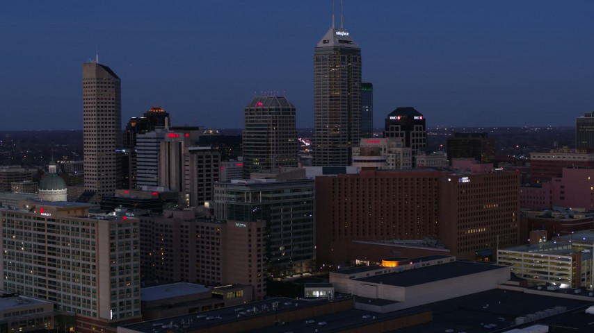 5.7K stock footage aerial video fly away from city skyline at twilight, reveal factory with smoke stacks, Downtown Indianapolis, Indiana Aerial Stock Footage | DX0001_002965