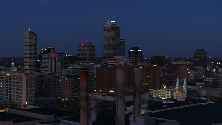 5.7K aerial video flyby giant skyscrapers of the city skyline at twilight, reveal smoke stacks, Downtown Indianapolis, Indiana Aerial Stock Footage DX0001_002970