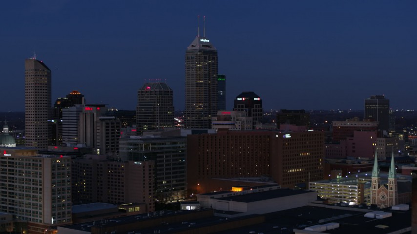 5.7K aerial video pass giant skyscrapers of the city skyline at twilight, seen from smoke stacks, Downtown Indianapolis, Indiana Aerial Stock Footage | DX0001_002971