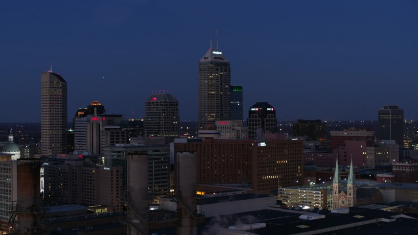 5.7K aerial video reverse view of giant skyscrapers of the city skyline at twilight, seen from smoke stacks, Downtown Indianapolis, Indiana Aerial Stock Footage | DX0001_002972