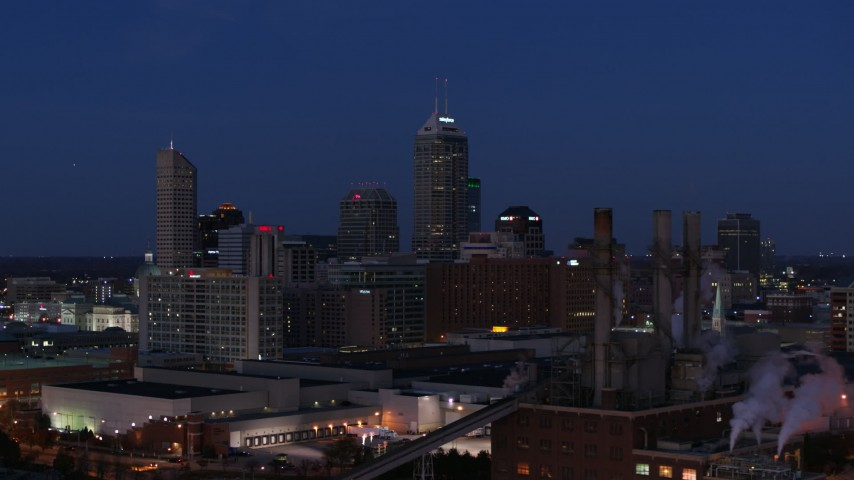 5.7K stock footage aerial video of giant skyscrapers of the city skyline at twilight, seen from factory smoke stacks, Downtown Indianapolis, Indiana Aerial Stock Footage | DX0001_002973