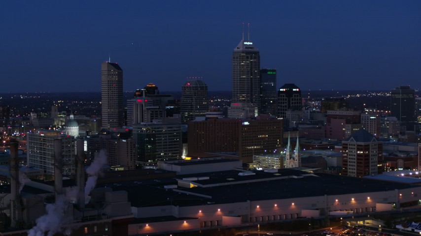 5.7K aerial video flyby smoke stacks and skyscrapers of the city skyline at twilight, Downtown Indianapolis, Indiana Aerial Stock Footage | DX0001_002975