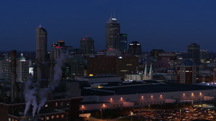 5.7K stock footage aerial video flyby smoke stacks and the city skyline during descent at twilight, Downtown Indianapolis, Indiana Aerial Stock Footage | DX0001_002976