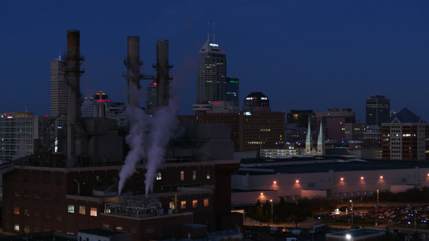 5.7K aerial video descend by factory smoke stacks with view of the city skyline at twilight, Downtown Indianapolis, Indiana Aerial Stock Footage | DX0001_002977
