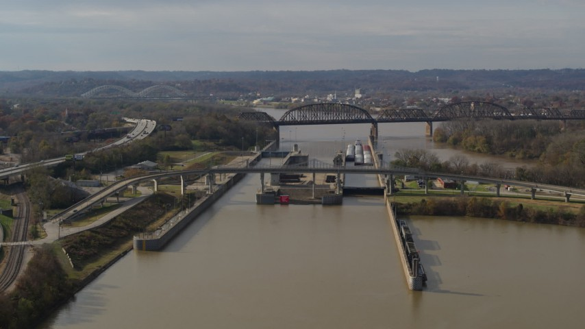 5.7K aerial video reverse view of locks and a dam on the Ohio River in Louisville, Kentucky Aerial Stock Footage | DX0001_003013