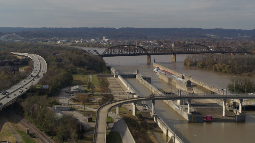 5.7K stock footage aerial video flying by railroad bridge near locks and a dam on the Ohio River in Louisville, Kentucky Aerial Stock Footage | DX0001_003016