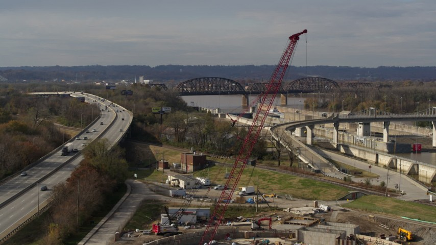5.7K stock footage aerial video construction crane near railroad bridge and locks and a dam on the Ohio River in Louisville, Kentucky Aerial Stock Footage | DX0001_003017