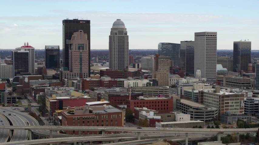 5.7K stock footage aerial video descend near freeway offramp with view of city skyline in Downtown Louisville, Kentucky Aerial Stock Footage | DX0001_003018