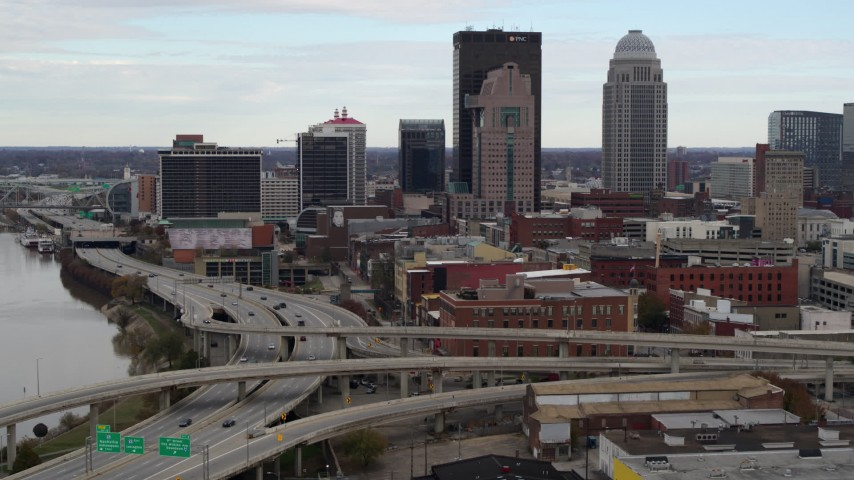 5.7K aerial video descend near freeway with view of skyscrapers in Downtown Louisville, Kentucky Aerial Stock Footage | DX0001_003023