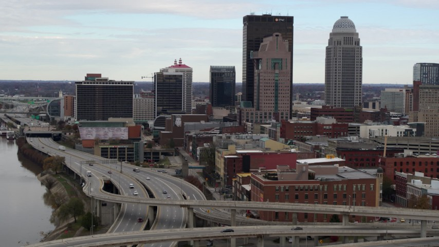 5.7K stock footage aerial video ascend over freeway with view of skyscrapers in Downtown Louisville, Kentucky Aerial Stock Footage | DX0001_003024