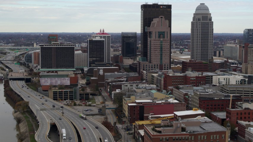 5.7K aerial video fly away from skyscrapers in Downtown Louisville, Kentucky, descend by freeway Aerial Stock Footage | DX0001_003025