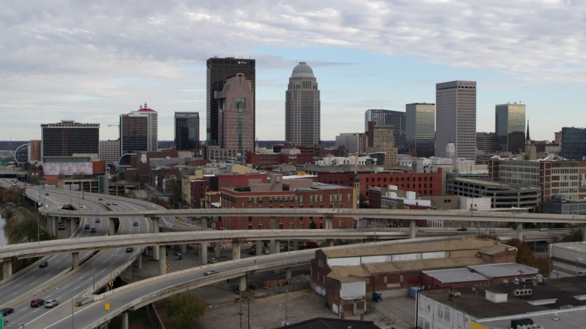 5.7K stock footage aerial video ascend over freeway to approach the city skyline in Downtown Louisville, Kentucky Aerial Stock Footage | DX0001_003026