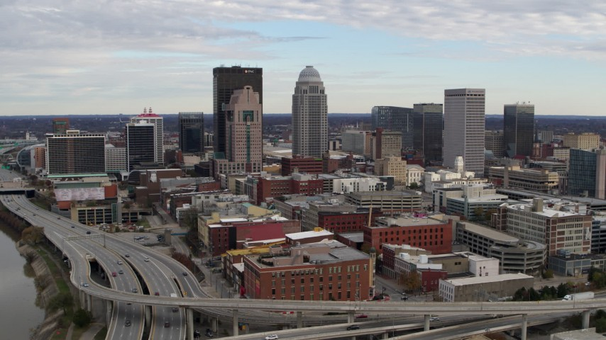 5.7K stock footage aerial video ascend and fly away from freeway and city skyline in Downtown Louisville, Kentucky Aerial Stock Footage | DX0001_003031