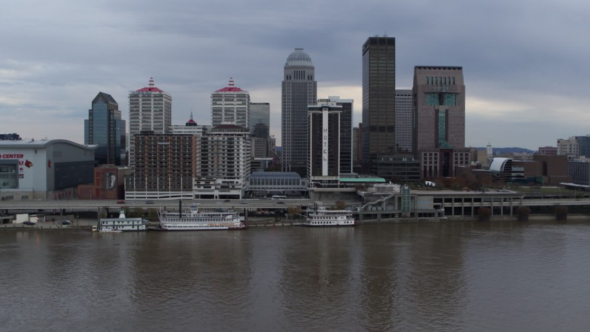 5.7K aerial video descend while flying by the city skyline and Ohio River in Downtown Louisville, Kentucky Aerial Stock Footage | DX0001_003046