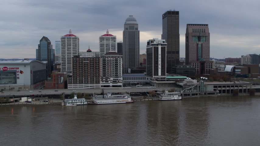 5.7K aerial video passing the city skyline beside the Ohio River during descent in Downtown Louisville, Kentucky Aerial Stock Footage | DX0001_003048