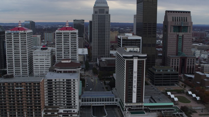 5.7K aerial video fly over Ohio River to approach skyline and hotel in Downtown Louisville, Kentucky Aerial Stock Footage | DX0001_003049