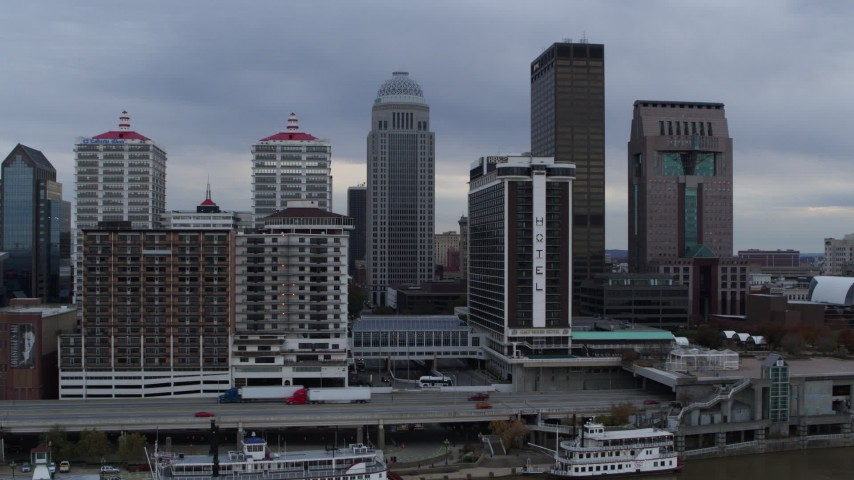 5.7K aerial video fly over Ohio River to approach riverfront hotel and skyscrapers in Downtown Louisville, Kentucky Aerial Stock Footage | DX0001_003051