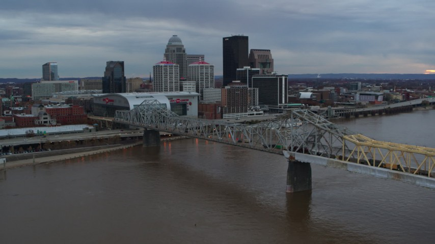 5.7K aerial video of the arena and city skyline seen from a bridge spanning Ohio River at sunset, Downtown Louisville, Kentucky Aerial Stock Footage | DX0001_003066